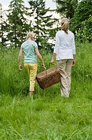 Mother and daughter with picnic basket in field