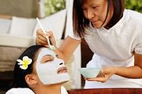 Beautician applying facial mask to woman's face