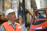 Foreman using cell phone in warehouse