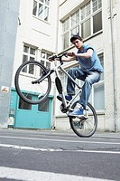 Young man doing a wheelie