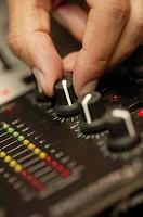 Disc Jockey turning dial on sound board
