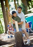 Father helping son chop wood