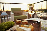 Tray of cheese and glasses of wine on rooftop patio