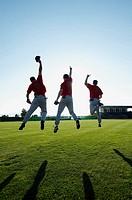 Baseball players jumping on field