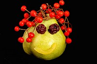 Character made of vegetables pear face with boisenberries eyes, red berries hair ans peach mouth