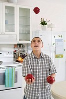 Boy juggling red apples