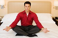 Man meditating in hotel room