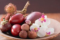 Assorted exotic fruits in a dish with orchids