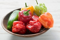 Mixed peppers and chillies in wooden dish