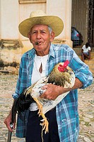 Old man smoking a cigar, carrying a cockerel, Trinidad, Sancti Spiritus Province, Cuba