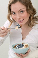 Woman eating muesli with blueberries