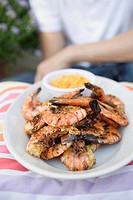 Grilled shrimps on plate, man in background