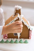 Child decorating gingerbread house with piping bag