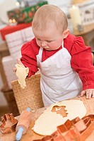Baby holding cut_out Christmas biscuit