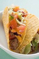 Two mince tacos in white dish close_up