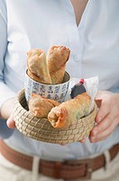 Woman holding basket of spring rolls and soy sauce