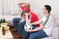Football fans, disappointed and excited, watching TV