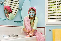 Preteen girl with facial mask painting her toenails