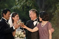 Bride and groom toasting outdoors with their parents