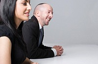 young businesswoman sitting at conference table with male colleague