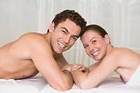young couple lying on massage bench smiling at camera