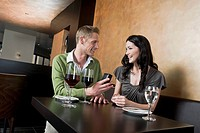 young couple sitting at restaurant man giving woman ring