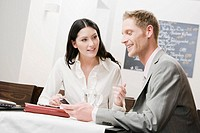businesswoman and male colleague having conversation at restaurant