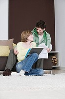 young couple reading documents at home together
