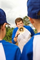 Coach yelling at young baseball players through megaphone