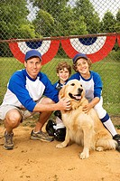 Baseball coach dad posing with sons and dog