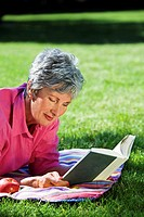 Senior woman lying on blanket while reading outdoors
