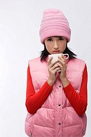 Young woman in pink hat and vest with coffee cup
