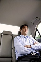 Businessman asleep in backseat of car