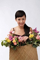 Young woman holding straw bag full of flowers
