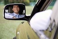 Reflection of smiling man in car rear view mirror