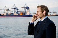 Businessman Using Cell Phone by Water