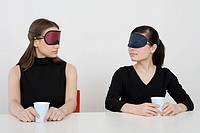 Two women wearing eye mask sitting at desk