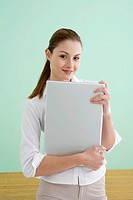 Businesswoman holding laptop, smiling, portrait