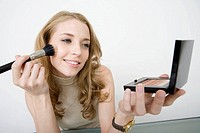 Young business woman applying make-up to face, portrait, close-up