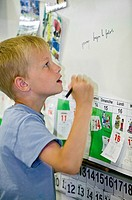 Young boy writing on a board at school