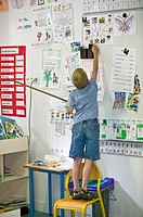 Young boy standing on a chair, facing a board and trying to catch something