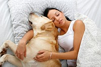Woman with Labrador Retriever in bed