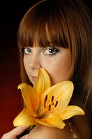 Romantic young woman with chestnut_coloured hair and make_up holding an orange lily
