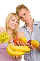 Smiling young blonde woman with long hair and a smiling young man holding colourful fruit in their hands