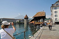 Tourists taking pictures, Kapellbruecke, Chapel Bridge, water tower, Reuss River, historic district, Lucerne, Switzerland, Europe