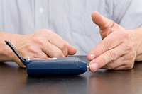 Hands and a measuring device, man measuring his blood sugar level
