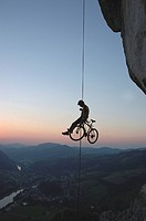 Extreme sport, a man abseiling with a bike in front of the sunset, Losenstein, Upper Austria, Austria, Europe