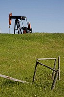 Crude oil pump in field with fence line in foreground. Alberta. Canada