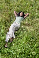 African woman relaxing in grass