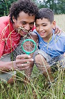 Mixed race father looking at spider web with son